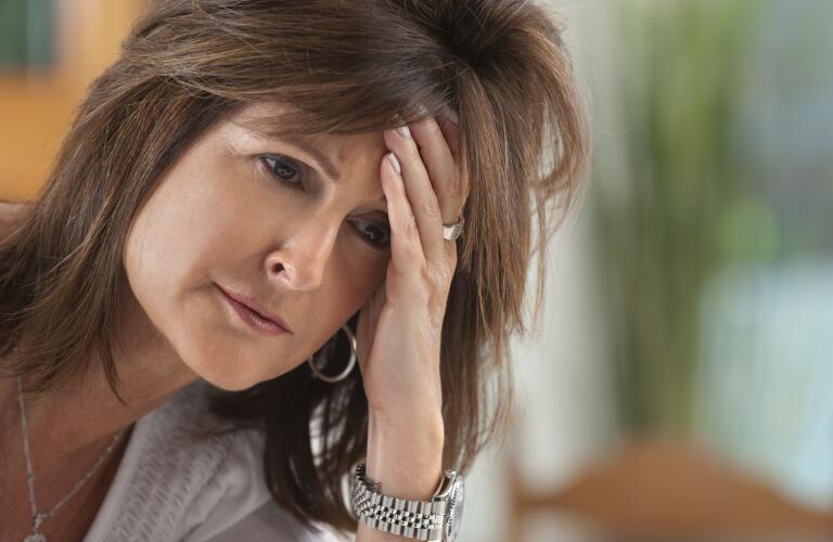 Middle aged woman looking concerned and holding forehead