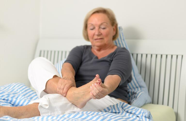 senior woman on bed holding foot