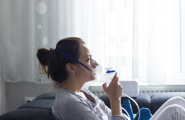 Young woman using asthma nebulizer on couch