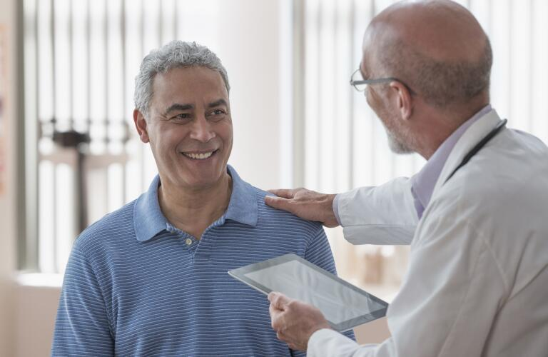 smiling-man-speaking-with-doctor-holding-tablet