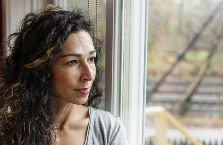 portrait of pensive woman looking out window