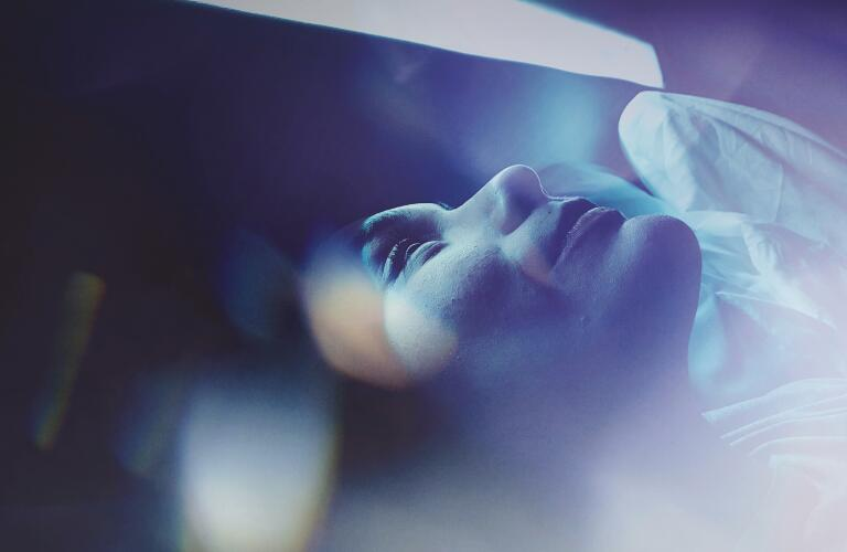 Close-Up Of Woman Sleeping On Bed with Blue Light Filter