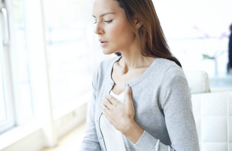 young woman with hand on chest and concern on face and trouble breathing