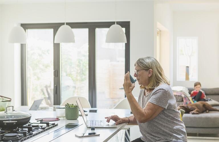 woman sitting at kitchen table in front of laptop using inhaler