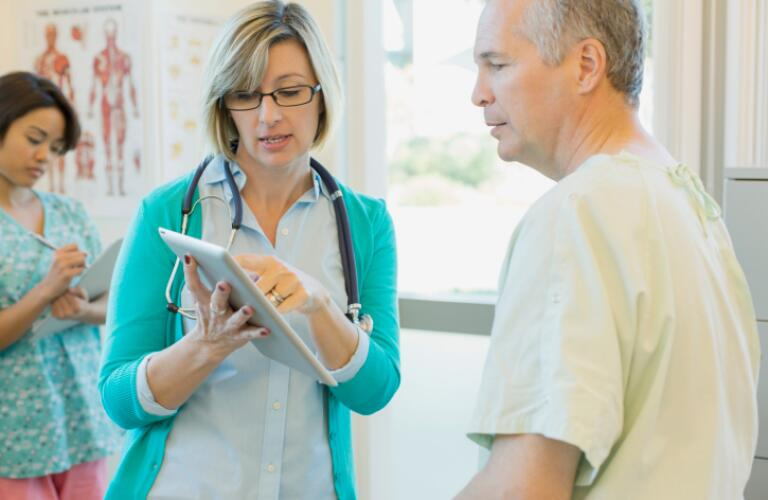 Female doctor explaining reports on digital tablet to patient with nurse writing notes in background