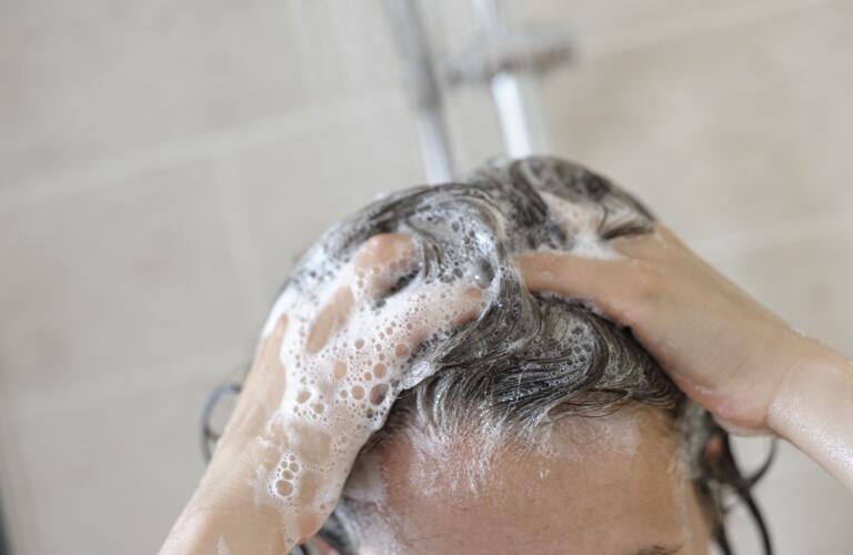 Unseen Caucasian woman shampooing hair in shower