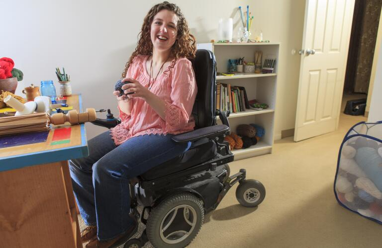 Young woman with muscular dystrophy in wheelchair at desk in bedroom