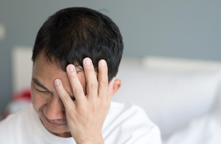 Asian American man holding front of head in pain