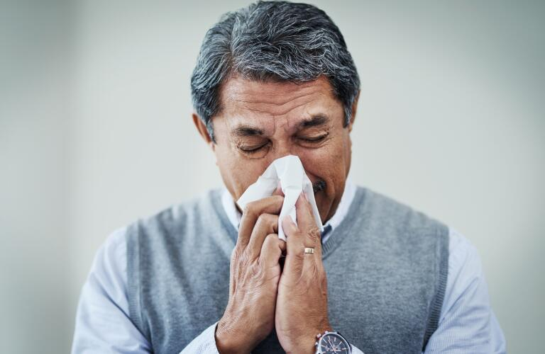 senior male blowing nose with tissue